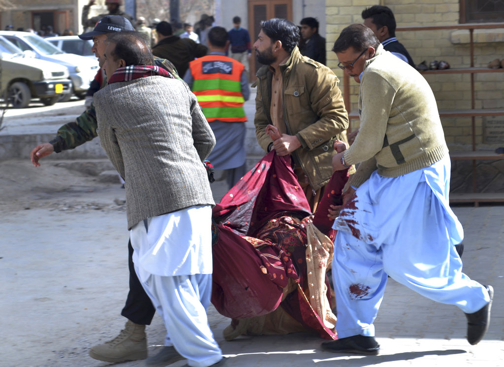A paramilitary soldier and volunteers rescue an injured women following a suicide attack on a church in Quetta, Pakistan, Sunday, Dec. 17, 2017. Two suicide bombers attacked the church when hundreds of worshippers were attending services ahead of Christmas. (AP Photo/Arshad Butt)