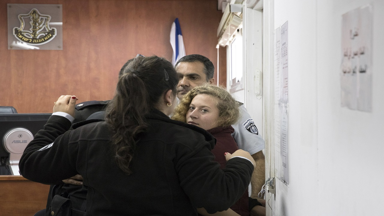 Palestinian Ahed Tamimi is escorted at a military court near Jerusalem, Wednesday, Dec. 20, 2017. The 16-year-old girl who is seen in a video kicking and pushing two Israeli soldiers near her West Bank home is being celebrated by Palestinians as a symbol of a new generation resisting a 50-year-old Israeli occupation.