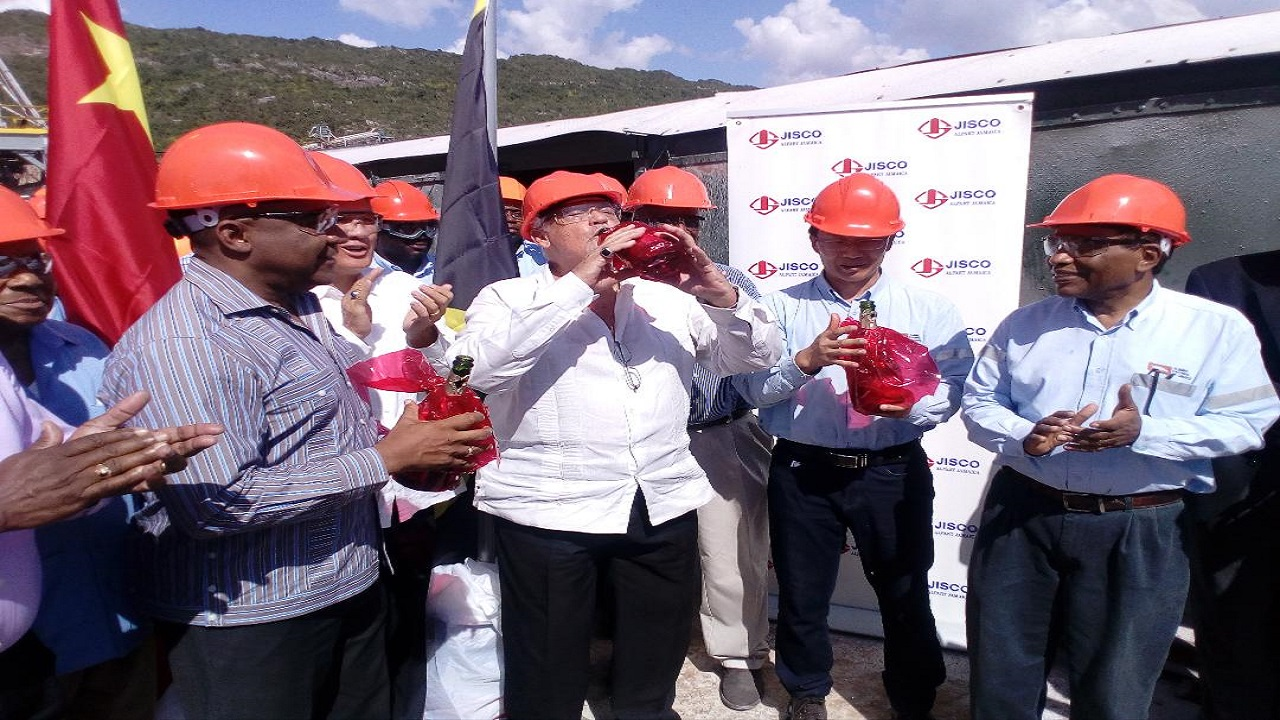 Transport and Mining Minister, Mike Henry (centre), takes a swig of a bottle of champagne on the loading platform at Port Kaiser as JISCO Alpart Jamaica refinery celebrated the first shipment of alumina from the plant in over eight years on Friday. Also pictured are key industry players, including Opposition Spokesman on Mining, Phillip Paulwell (second left foreground).