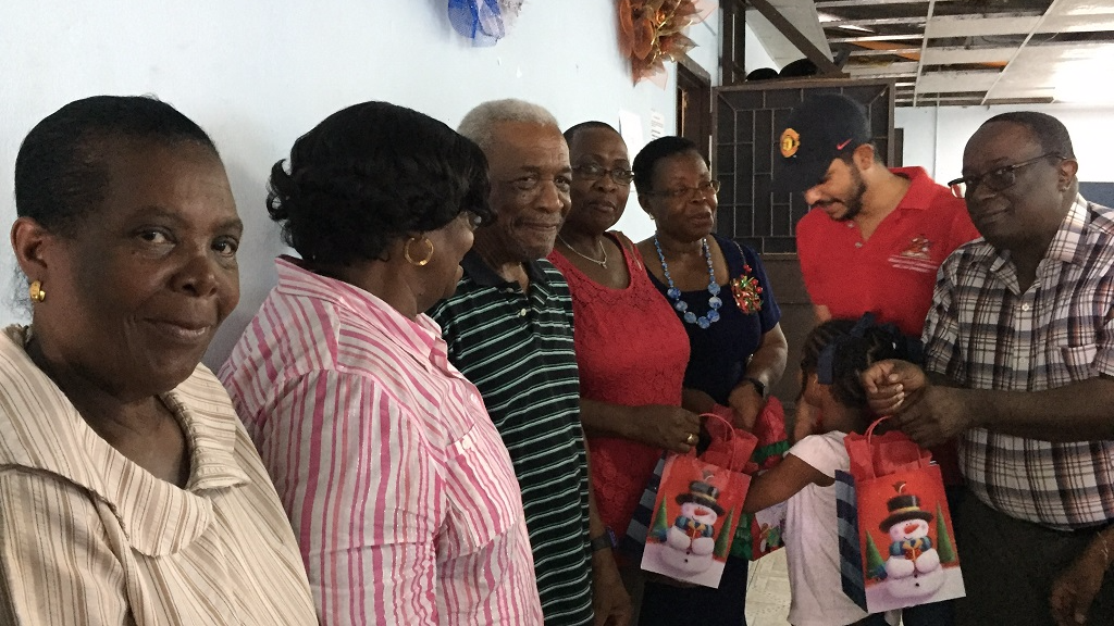 Photo: President of the La Romaine Community Council and National Volunteer Network Coordinator, Mr Matthew Kailah distributing Christmas presents to the specially invited guests and the elderly from the region. (Courtesy the Ministry of Rural Development and Local Government)