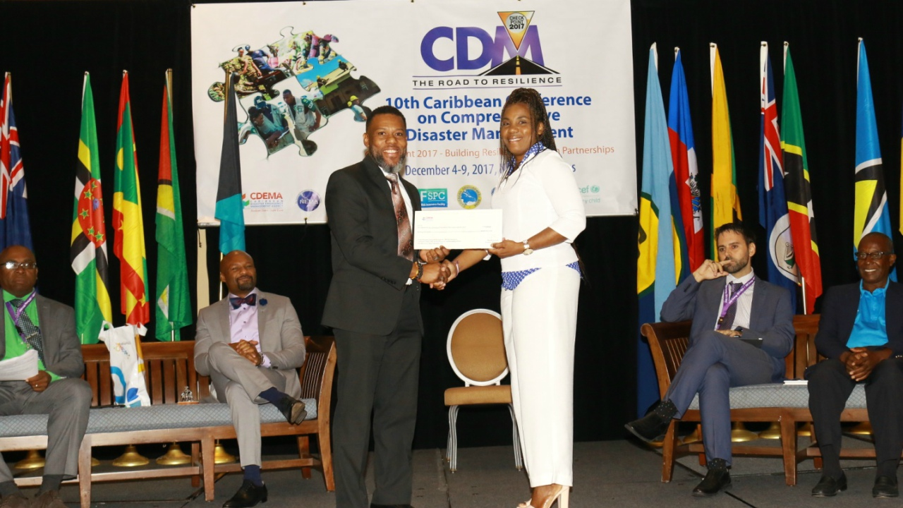 Deputy Director, Department of Disaster Management of the British Virgin Islands, Dr. Evangeline Inniss-Springer (left), accepting a cheque being presented by Ronald Jackson, Executive Director of Caribbean Disaster Emergency Management Agency (CDEMA) (right).
