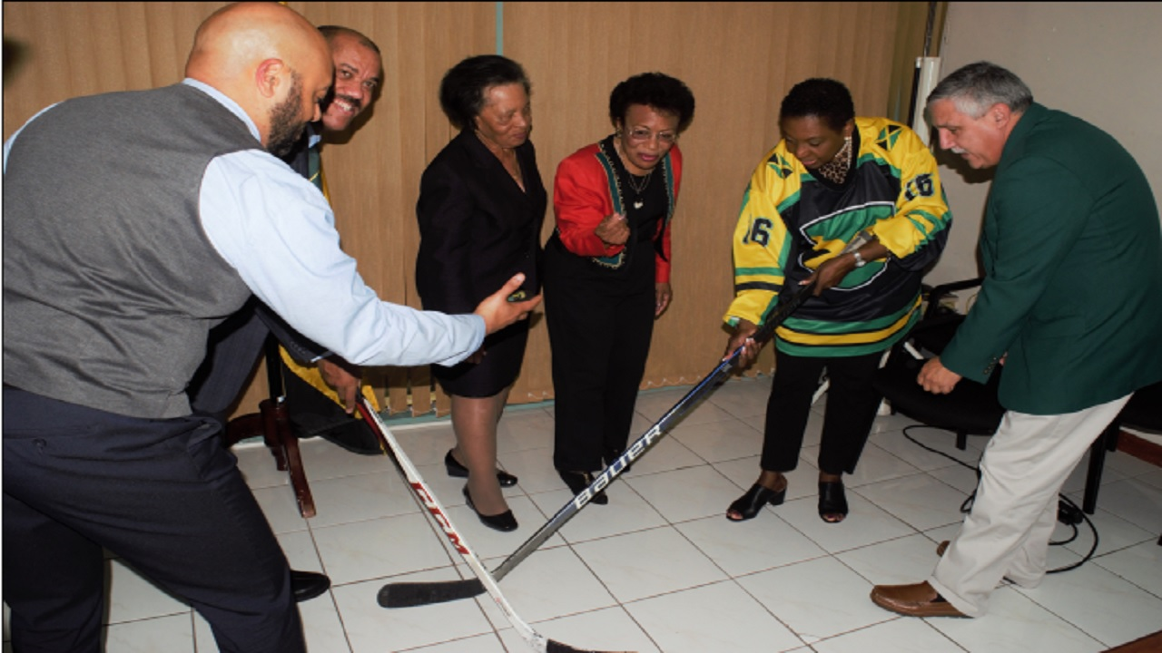 Sport Minister Olivia Grange prepares to poke the puck away from Greame Townsend, national hockey coach (2nd left) as it is being released by Donovan Tait, hockey player and coach (left). Looking on in anticipation are: Dorothy McLeod, Director, California Cultural Alliance (3rd left); founding members of the Jamaica Olympic Ice Hockey Federation Judith Smith (4th left) and Lester Griffin (right).