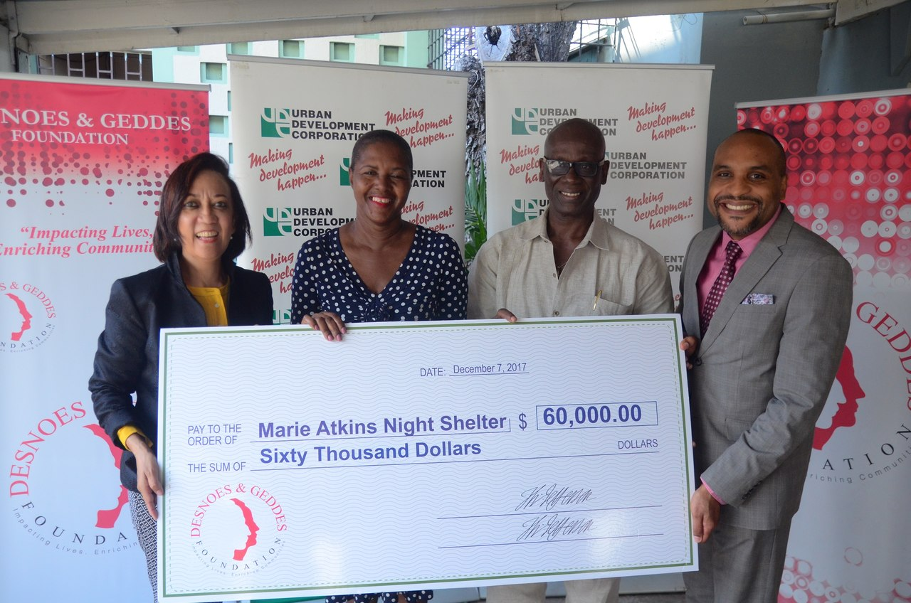 Dianne Ashton-Smith, Director, D&G Foundation (left) presents a donation of $60,000 to Mavis Farquharson Inspector of Poor, Marie Atkins Night Shelter (second left). Desmond McKenzie Minister of Local Government & Community Development (second left) and Robert Hill, Town Clerk, Kingston & St. Andrew Municipal Corporation were also in attendance for the presentation.