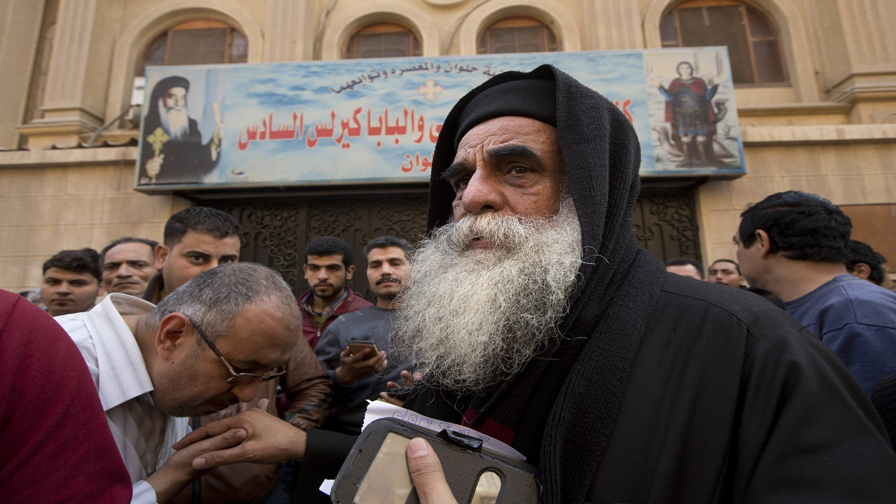 Priest David, the head of Mar Mina church, is greeted by people outside the chruch, in Helwan, Cairo, Egypt, Friday, Dec. 29, 2017, where at least 10 people, including eight Coptic Christians, have been killed in a shootout outside the church.