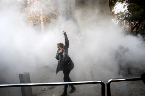In this photo a university student attends a protest inside Tehran University while a smoke grenade is thrown by anti-riot Iranian police in Tehran. (AP Photo)