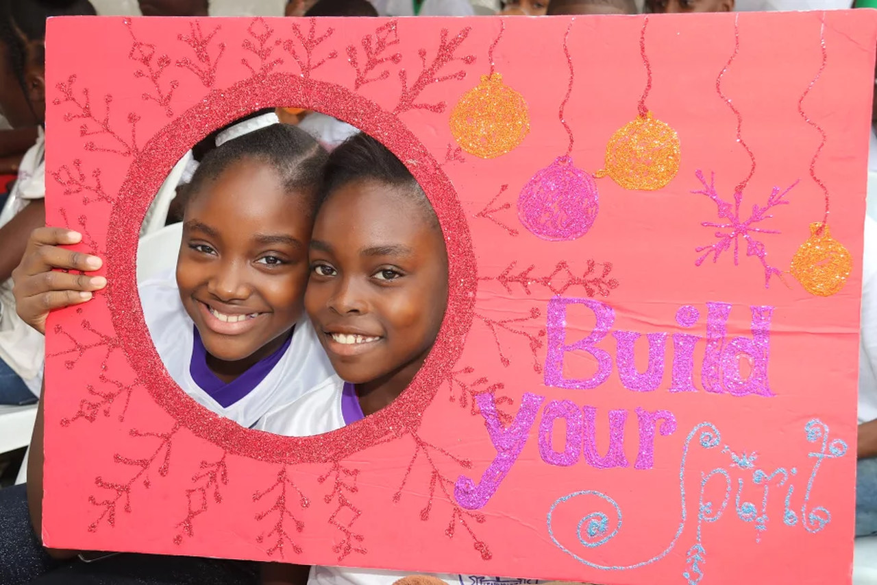 Race Course Primary's Ciarah Coleman and Sashauna Williams look through one of the face holes at the inspirational spot to 'Build our Spirit' at the JWN Foundation's annual Christmas treat dubbed 'FUN-spiration', at JWN's New Yarmouth base last week.