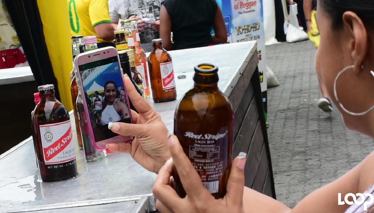 A MS Monarch passenger takes a selfie with a Red Stripe beer during a trip to Kingston on Monday.