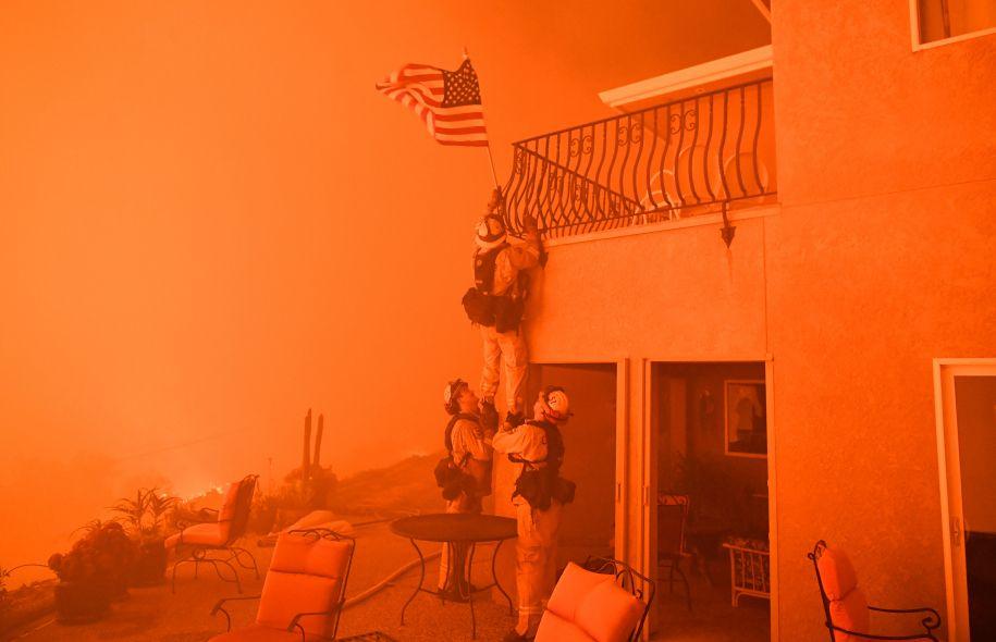 Des pompiers enlèvent un drapeau américain à Oroville, pendant que le foyer «Wall» fait rage. Photo: Josh Edelson Agence France-Presse