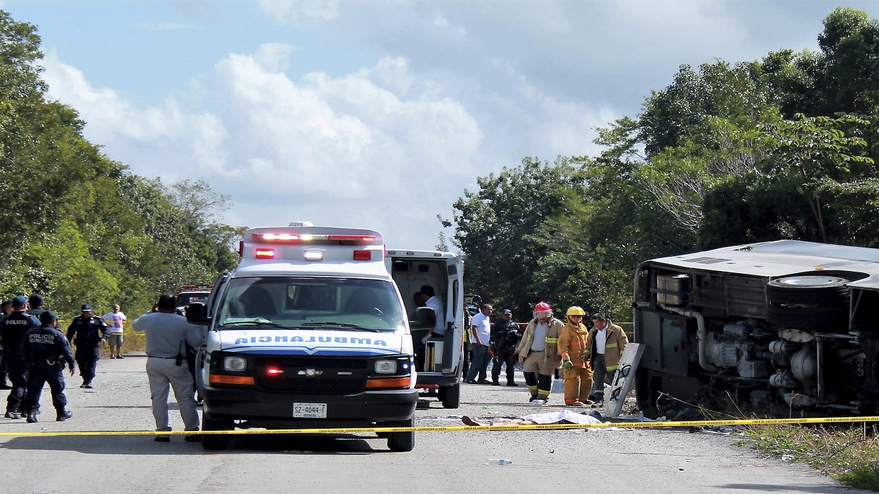 An ambulance sits parked next to an overturned bus in Mahahual, Quintana Roo state, Mexico, Tuesday, Dec. 19, 2017. The bus carrying cruise ship passengers to the Mayan ruins at Chacchoben in eastern Mexico flipped over on a highway early Tuesday.