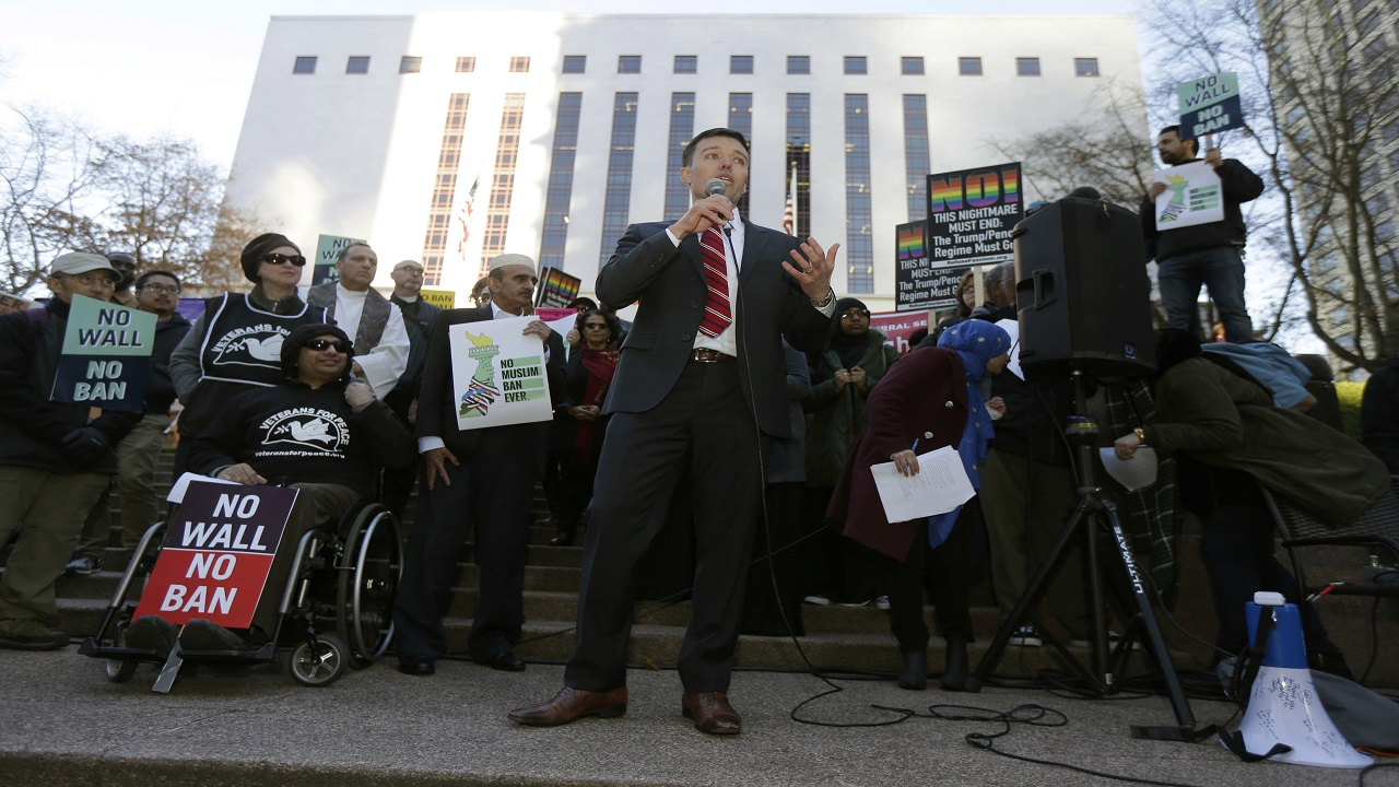 Washington Solicitor General Noah Purcell, center, speaks during a protest rally, Wednesday, Dec. 6, 2017, outside a federal courthouse in Seattle.
