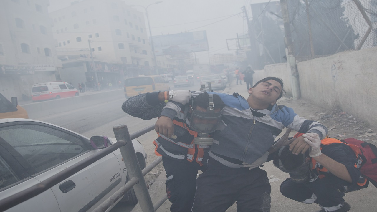 Two paramedics evacuate an injured Palestinian protester amid heavy teargas, during clashes with Israeli troops following protests against U.S. President Donald Trump's decision to recognize Jerusalem as the capital of Israel, at the outskirts of the West Bank city of Ramallah, Wednesday, Dec. 20, 2017.