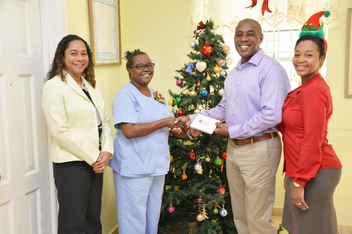 BIBA Charity Trustee Louisa Lewis-Ward (left), BIBA President Marlon Waldron (second from right) and BIBA Marketing and Communication Officer Mialisa Garnes (right) making the presentation to the Sterling Children's Home's House Parent, Marcia Burke (second from left).