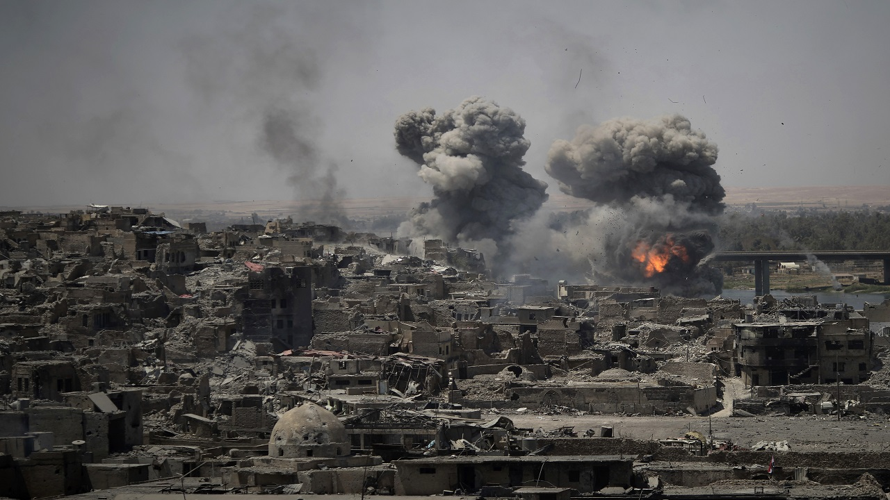 In this July 11, 2017 file photo, airstrikes target Islamic State positions on the edge of the Old City in Mosul, Iraq. Iraq said Saturday, Dec. 9, 2017 that its war on the Islamic State is over after more than three years of combat operations drove the extremists from all of the territory they once held.