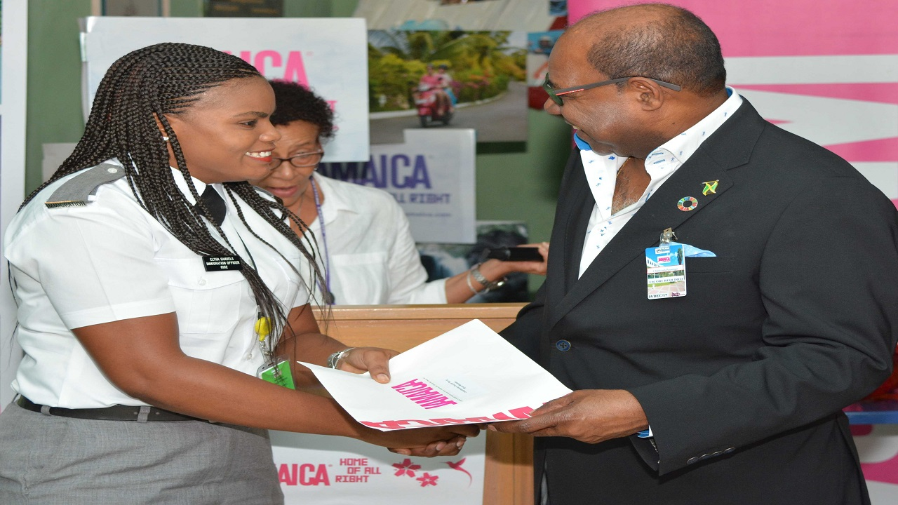 """Tourism Minister Edmund Bartlett (right) presents a prize to PICA Officer, Elsa Samuels with Margaret Jones in the background. The occasion was a """"thank you"""" breakfast by the Jamaica Tourist Board."""