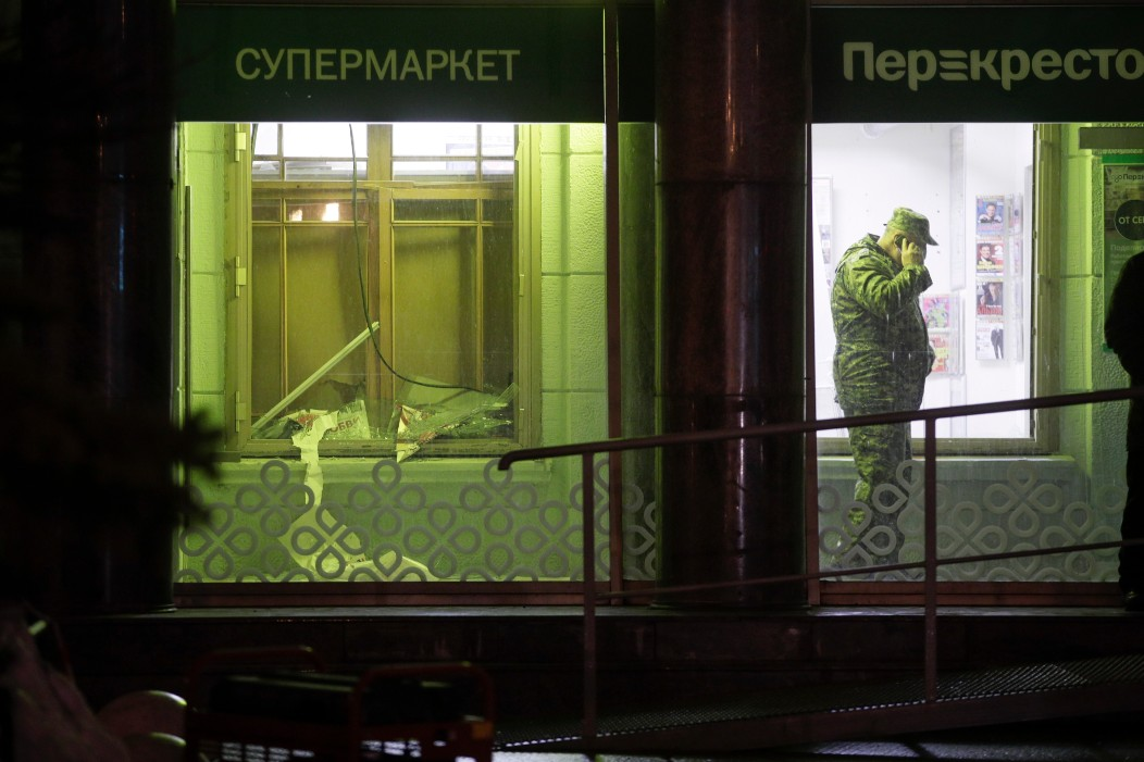 An investigator speaks on the phone inside a supermarket, after an explosion in St. Petersburg, Russia. (AP Photo/Dmitri Lovetsky)