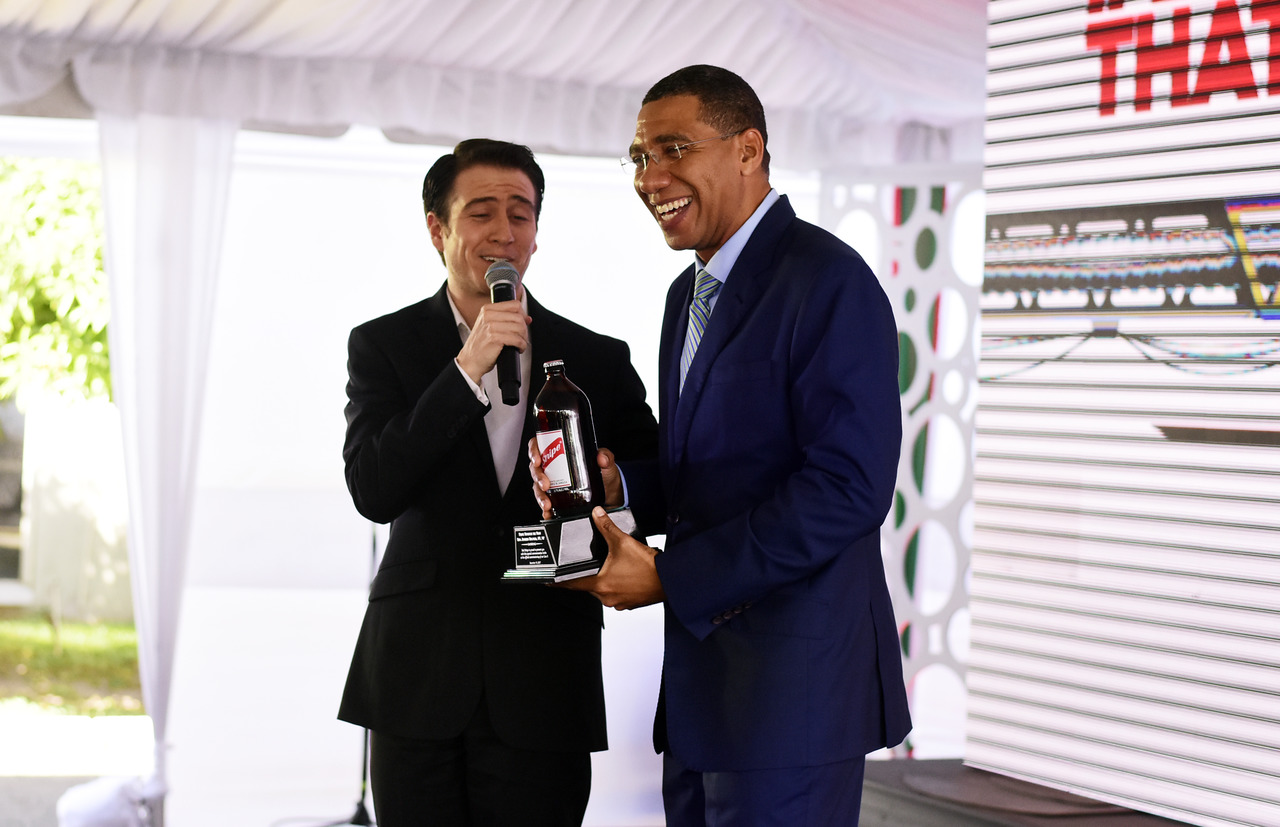 Prime Minister Andrew Holness is presented with a  commemorative beer from Red Stripe CEO Ricardo Nuncio.