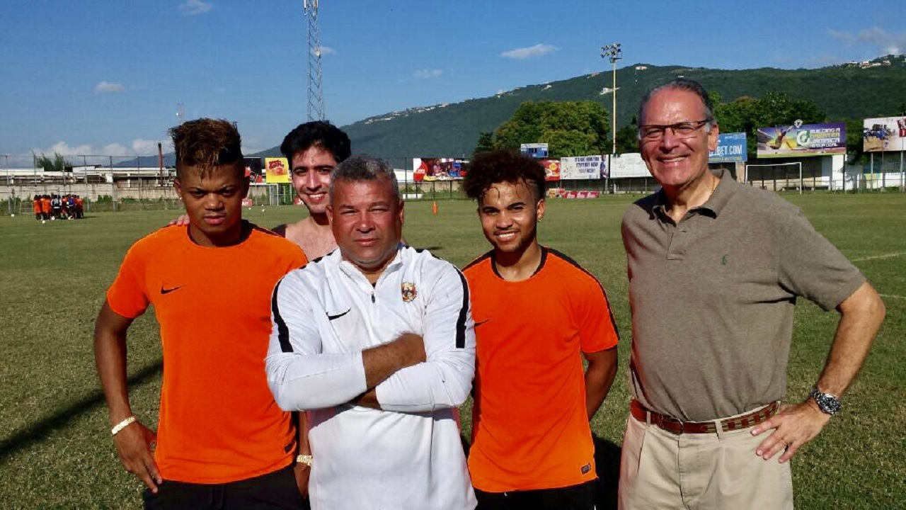 Phoenix Football Academy boss Craig Butler (centre), with Spanish Ambassador to Jamaica, Josep Maria Bosch Bessa (right) and his son Carlos Bosch (second left), and the club's players Leon Bailey (left) and Kyle Butler. The ambassador's son joined the Phoenix Elites for a game of football at the Waterhouse field in St Andrew.