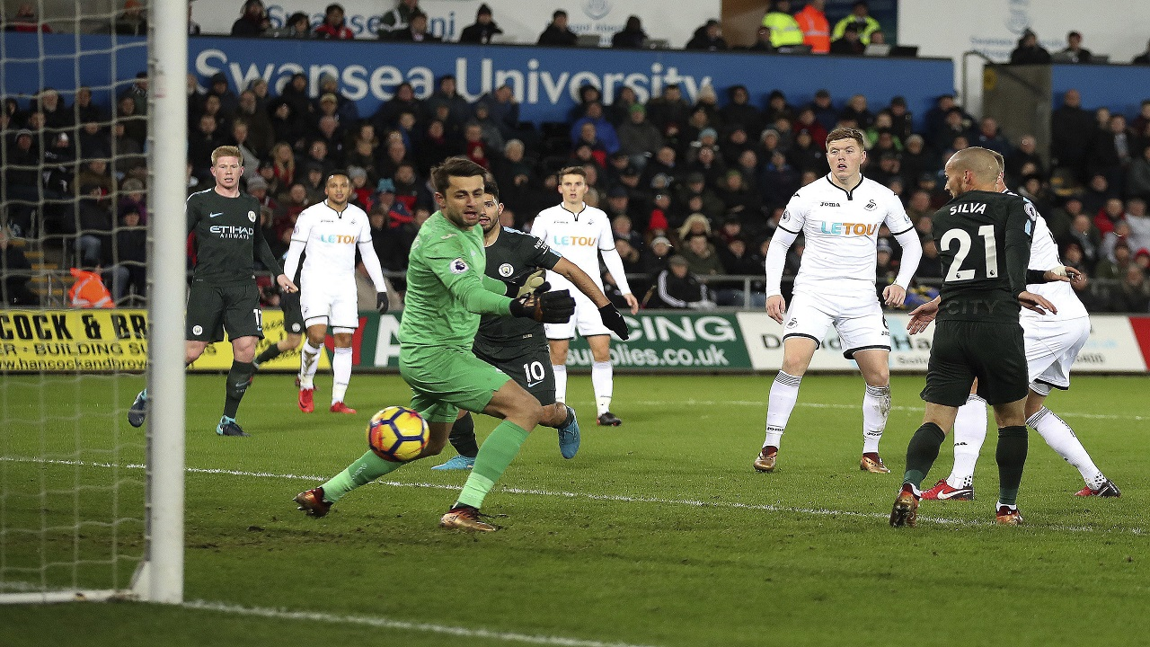 Manchester City's David Silva, right, scores against Swansea City, during their English Premier League football match at the Liberty Stadium in Swansea, England, Wednesday Dec. 13, 2017.