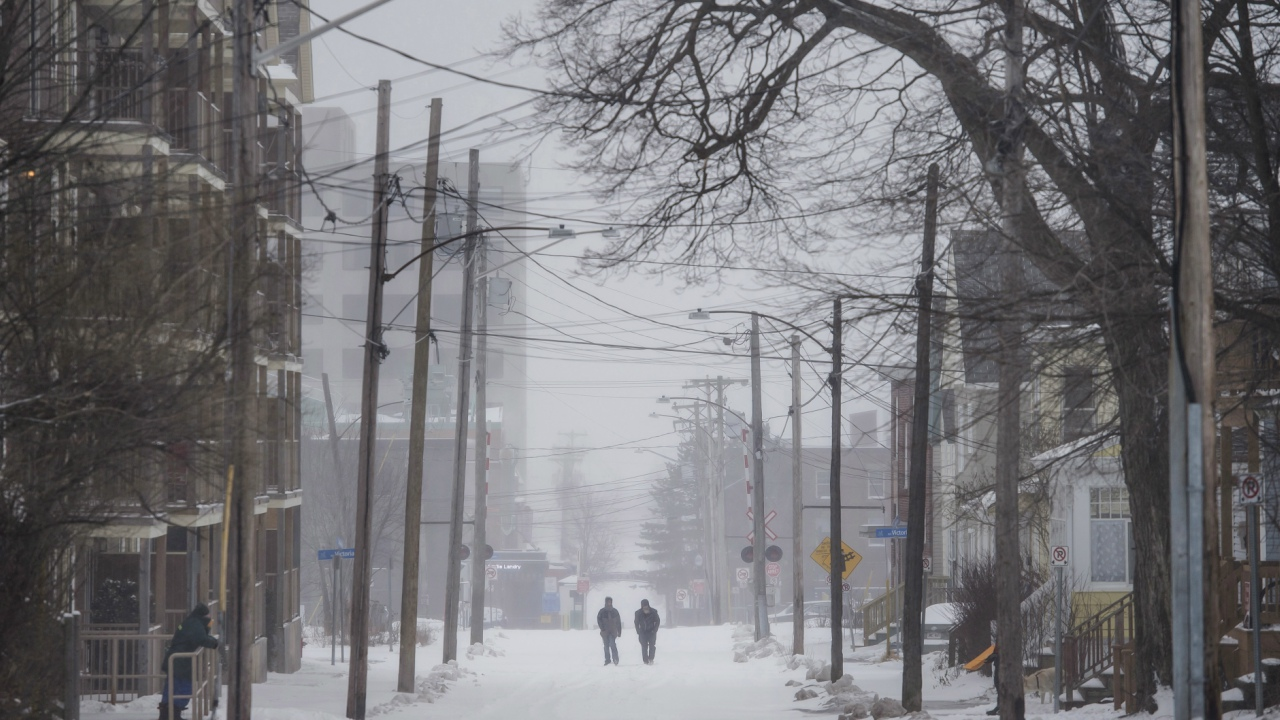 Pedestrians walk down the centre of the road in Moncton, New Hampshire, as a winter storm blows through Atlantic Canada on Christmas Day. (Darren Calabrese/The Canadian Press via AP)