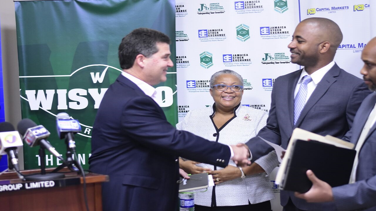 Wisynco Chairman William Mahfood (left) greets the CEO of NCB Capital Markets Steven Gooden (second right) as JSE Managing Director Marlene Street Forrest (centre) looks on.