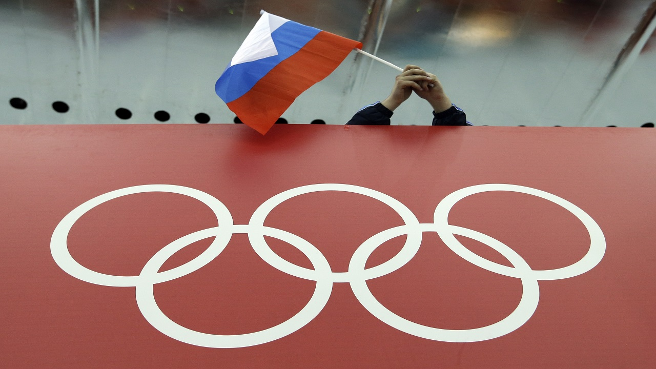 In this Feb. 18, 2014, file photo, a Russian skating fan holds the country's national flag over the Olympic rings before the start of the men's 10,000-meter speedskating race at Adler Arena Skating Center during the 2014 Winter Olympics in Sochi, Russia.