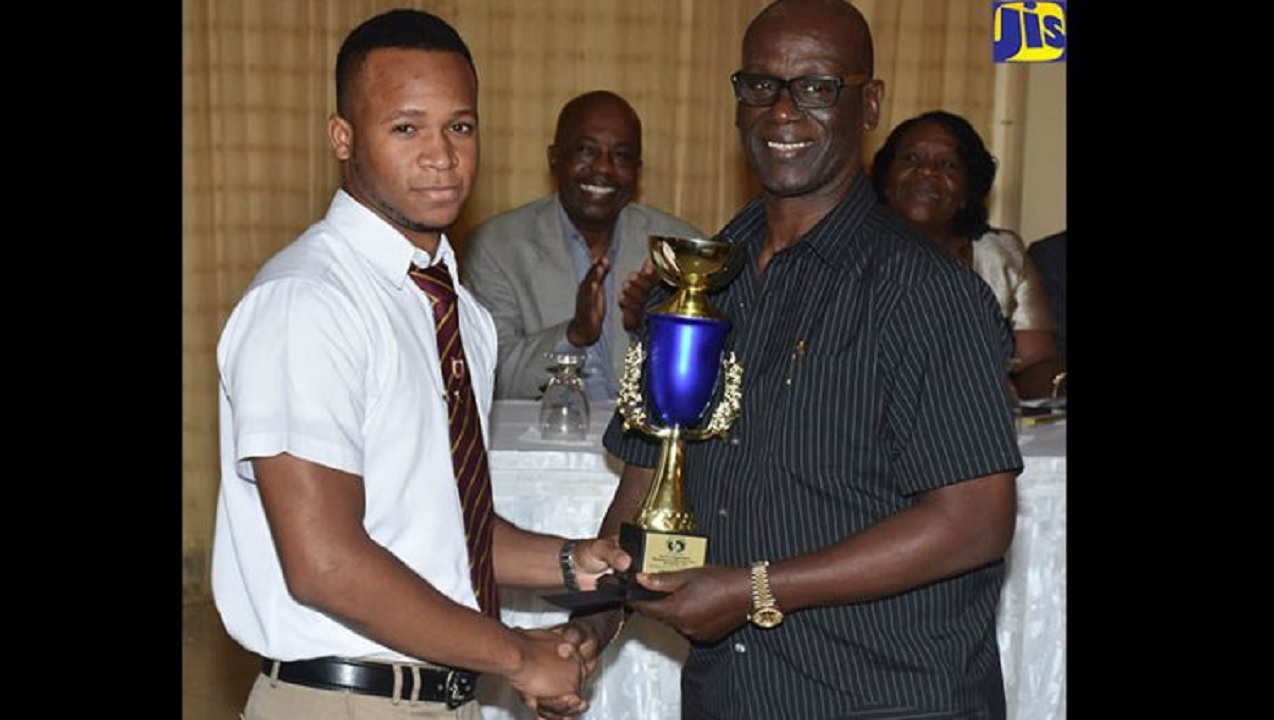 Minister of Local Government, Desmond McKenzie (right), presents an award to Renaldo Facey at the Board of Supervision/Poor Relief Association Awards and Recognition Ceremony, held on November 28 at the Mona Visitors' Lodge in St Andrew. (PHOTO: JIS)
