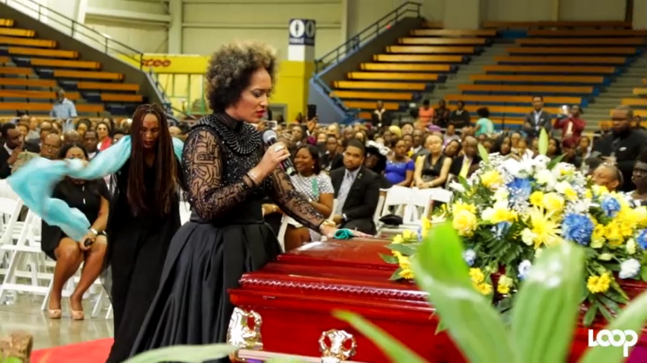 Kelly-Ann Boyne touches the casket with the remains of her father, Ian, at the late journalist's funeral service on Sunday.