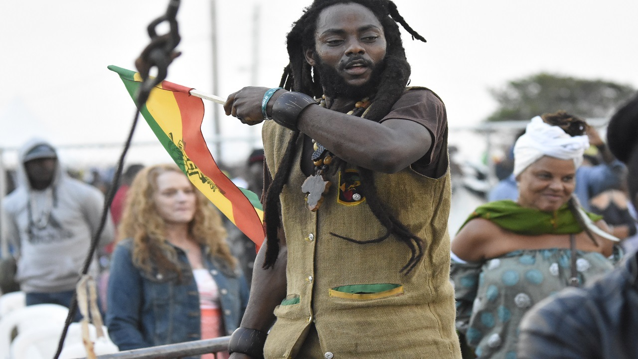 A Rastafarian man waves a flag on Saturday morning during the 25th staging of Rebel Salute at Grizzly's Plantation Cove in St Ann. (PHOTO: Marlon Reid)