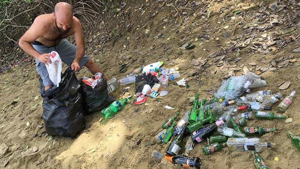 One visitor worked hard on New Year's Day to clean up empty beer and champagne bottles, along with other bits of garbage, at Grafton Beach, Tobago.