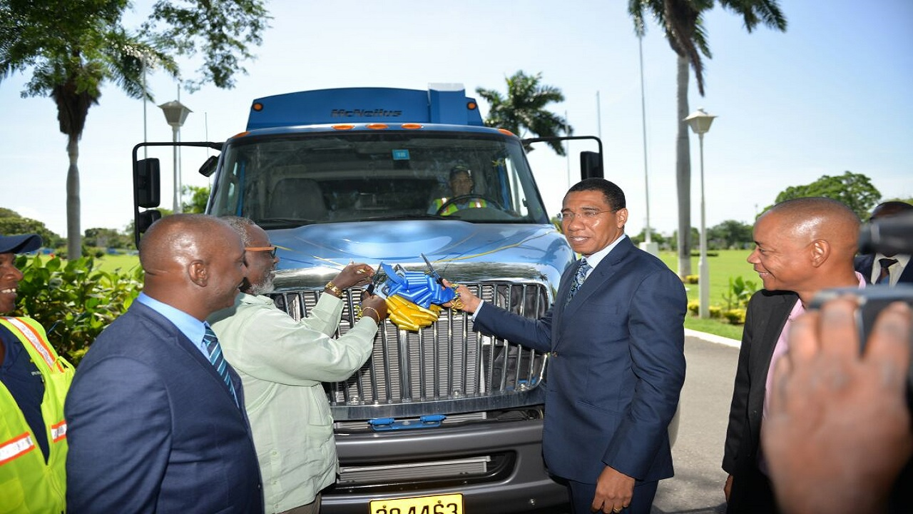 Prime Minister Andrew Holness (second right) and Local Government Minister Desmond McKenzie (second left) cut a ribbon to introduce one of the new compactor garbage trucks that were added to the NSWMA's fleet last October. NSWMA chairman, Dennis Chung (right), and Executive Director Audley Gorden look on. (file photo)