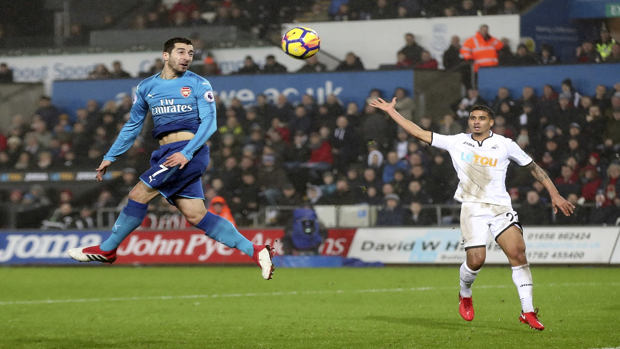 Arsenal's Henrikh Mkhitaryan, left, heads the ball on goal during the English Premier League football match against Swansea City at the Liberty Stadium, Swansea, Wales, Tuesday, Jan. 30, 2018.