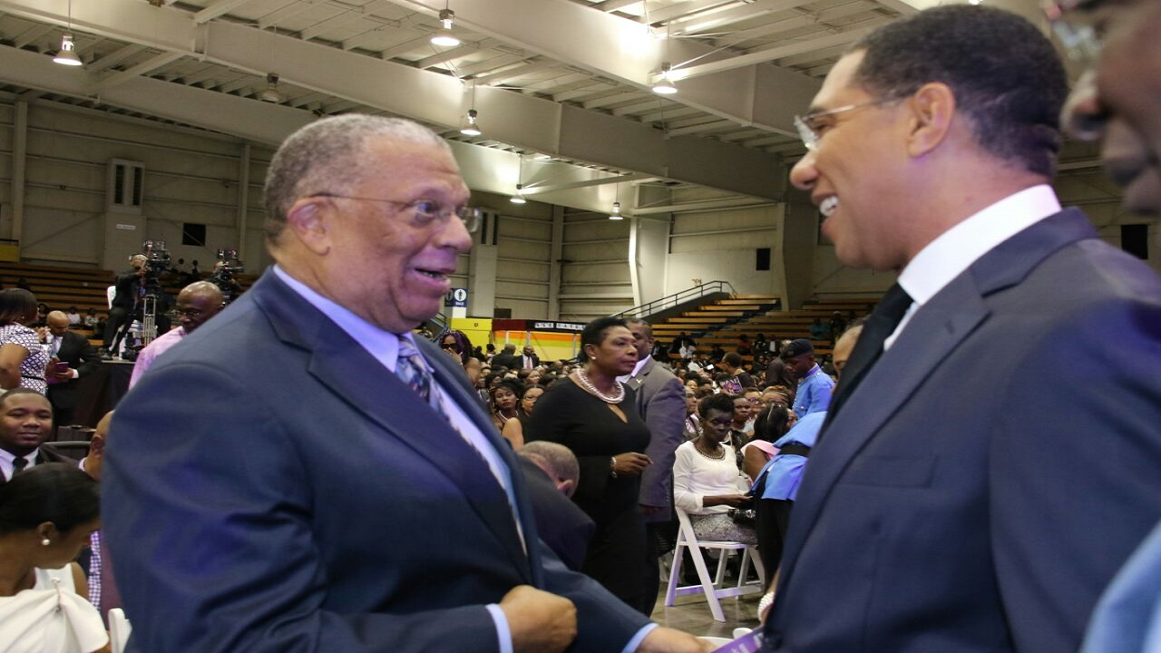 Prime Minister Andrew Holness (right) and Opposition Leader, Dr Peter Phillips, exchange pleasantries at Ian Boyne's funeral service now on at the National Indoor Sports Centre in St Andrew.