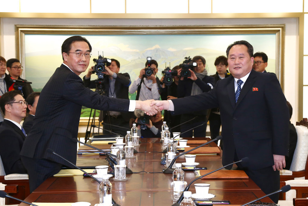 South Korean Unification Minister Cho Myoung-gyon, left, poses with head of North Korean delegation Ri Son Gwon while shaking hands during their meeting at the Panmunjom in the Demilitarized Zone in Paju, South Korea. (Korea Pool via AP)