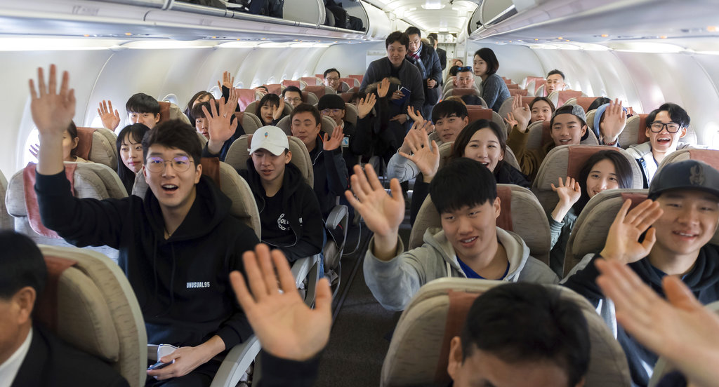 South Korean skiers on the chartered flight wave to the media before taking off to North Korea at Yangyang International Airport in Yangyang, South Korea. (Korea Pool/Yonhap via AP)