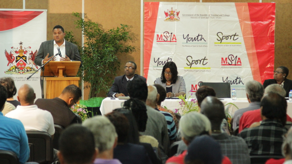 Hon. Darryl Smith, Minister of Sport & Youth Affairs delivers remarks at the seminar for NGBs. To his right is MSYA Legal Officer Tyrone Marcus and Deputy Permanent Secretary Marcia London-McKellar.