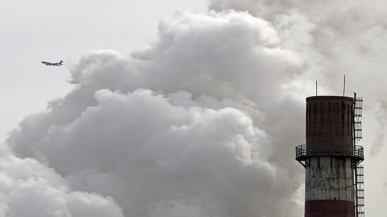 In this Feb. 28, 2017 file photo, a passenger airplane flies behind steam and white smoke emitted from a coal-fired power plant in Beijing. On Monday, Nov. 13, 2017, scientists projected that global carbon pollution has risen in 2017 after three straight years when the heat-trapping gas didn't go up at all.