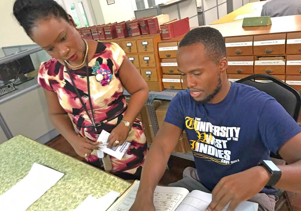 (L-R) Senior Archivist at the Barbados Department of Archives, Stacia Adams, assisting Rashaun Allen.
