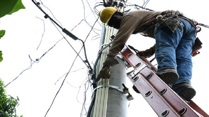 A Jamaica Public Service workman servicing power lines (file photo).
