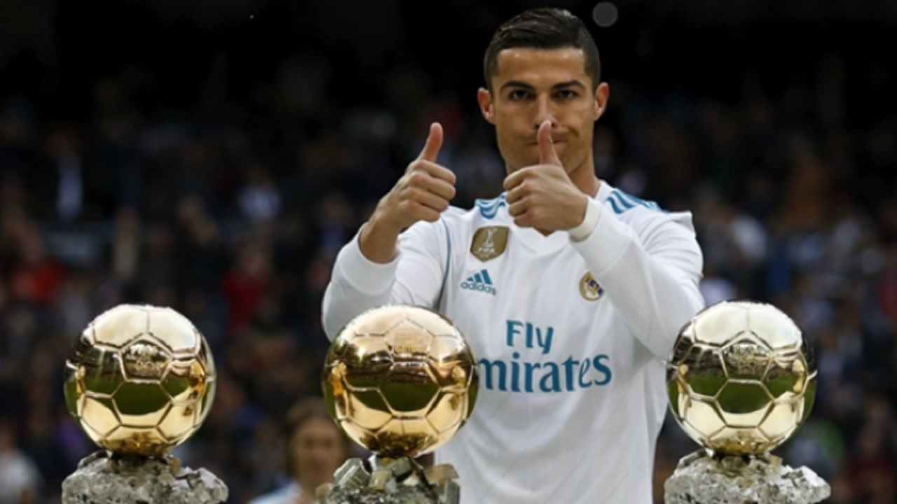 Cristiano Ronaldo shows off three of his five Ballons d'Or.