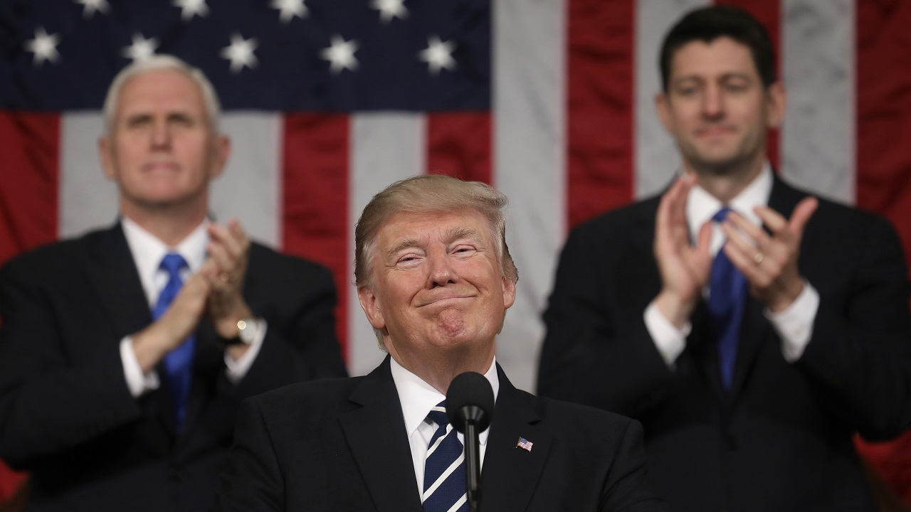 In this 28 February 2017 image, President Donald Trump addresses Congress, as Vice President Mike Pence and House Speaker Paul Ryan applaud.