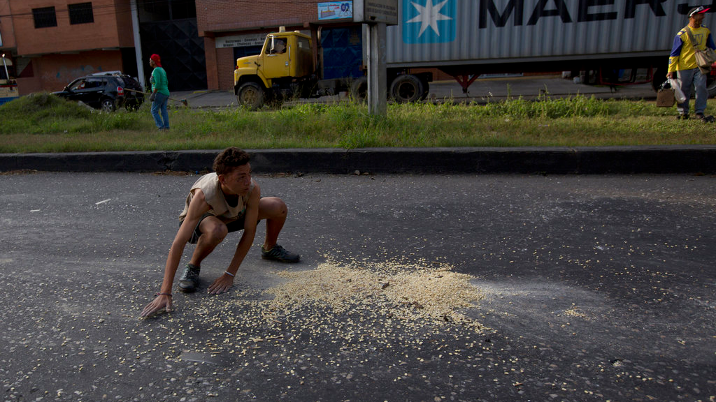 A youth moves quickly to collect grains of corn on the street that fell from a truck that was looted outside the port in Puerto Cabello, Venezuela. (AP Photo/Fernando Llano)