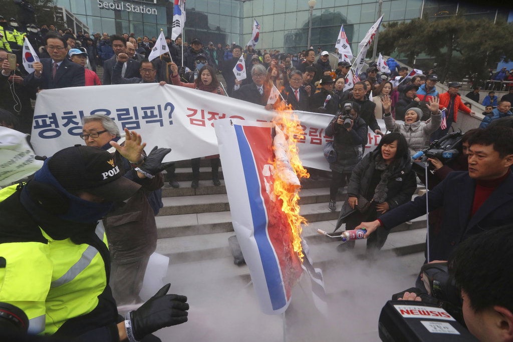 South Korean protesters burn a North Korean flag during a rally against a visit of North Korean Hyon Song Wol, head of a North Korean art troupe, in front of Seoul Railway Station in Seoul, South Korea. (AP Photo/Ahn Young-joon)