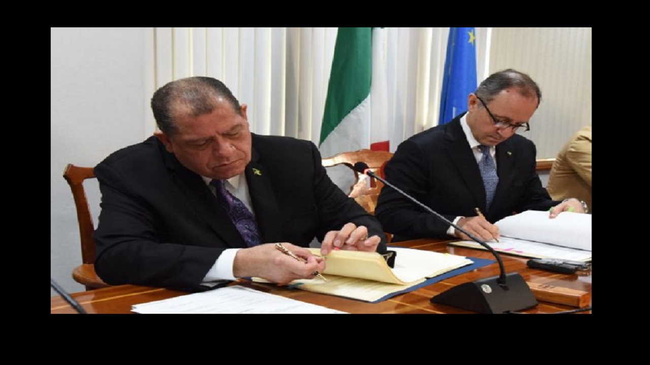 Minister of Finance and the Public Service Audley Shaw (left), prepares to sign the agreement for the elimination of double taxation between Jamaica and Italy at the Ministry's offices in Kingston on Friday. Ambassador of the Republic of Italy to Jamaica, Armando Varracchio (right), affixes his signature. Photo via Jamaica Information Service.