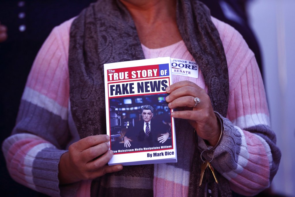 """FILE- In a Nov. 17, 2017 file photo, a supporter holds up a """"Fake News"""" book while Kayla Moore, wife of U.S. Senate candidate Roy Moore, speaks at a press conference in Montgomery, Ala. (AP Photo/Brynn Anderson_File)"""