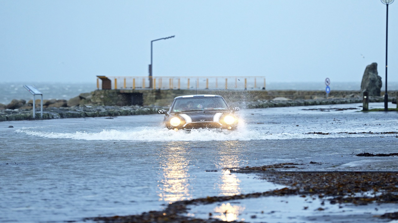 A car drives through a flooded car park in Salthill, Galway, Ireland Wednesday Jan. 3, 2018 as Storm Eleanor lashed Britain and Ireland with violent storm-force winds of up to 100mph, leaving thousands of homes without power and hitting transport links.