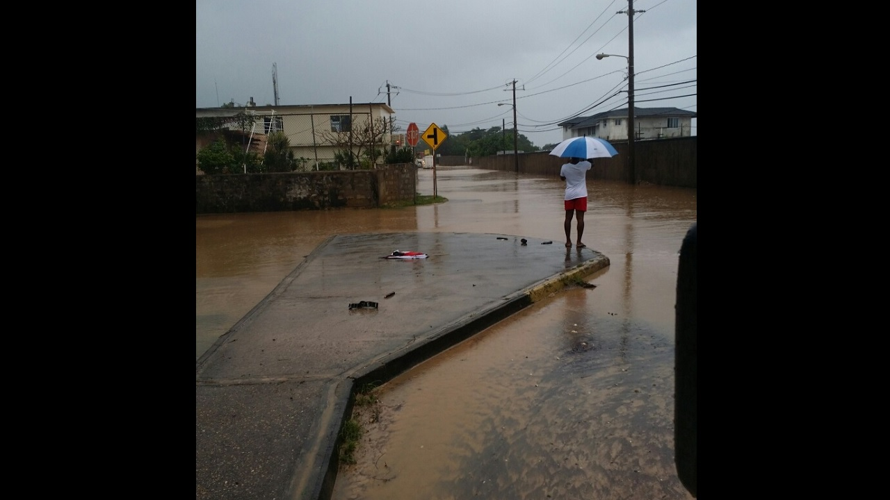 A woman looks at flood waters in Runaway Bay, St Ann on  Thursday morning.