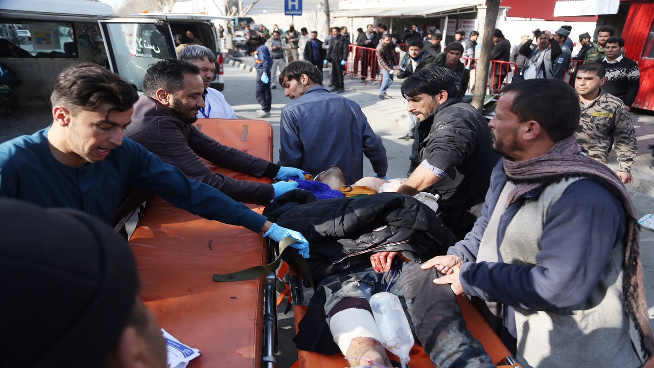People help carry an injured man to the hospital following a suicide attack in Kabul, Afghanistan, Saturday Jan. 27, 2018. The Public Health Ministry says over a dozen were killed, and over 100 wounded ina suicide car bombing in downtown Kabul.