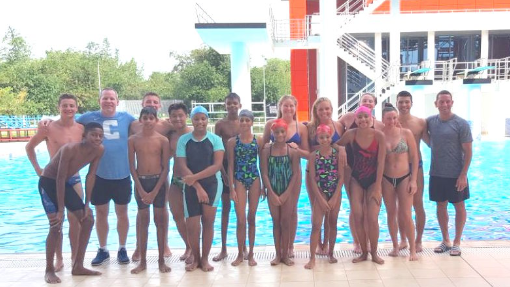 Local swimmers (front row) pose for a photo with Duke athletes and coach Esposto (extreme right)