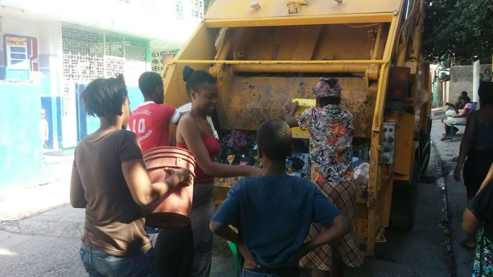 Des citoyens déversent des ordures dans un camion compressif. Photo : Facebook/ Maire de Port-au-Prince.