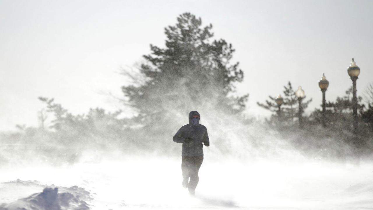 Gusty wind picks up snow accumulated on the ground as Jesse Sherwood, of Jersey City, N.J., jogs at Liberty State Park. (AP Photo/Julio Cortez)